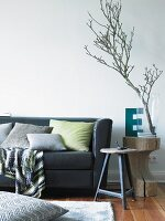 Floor cushion on rug in front of black leather sofa next to rustic side table; branch in glass vase