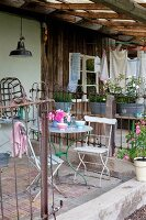 Metal chairs and table on veranda with old metal grille fence in front of small, rustic house with rendered and wood-clad walls