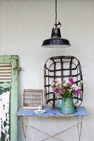 Bouquet in vintage enamel coffee pot on old garden table and metal basket leaning against white wall