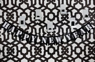 Wall decorated with graphic black and white wallpaper, party garland & candle sconces