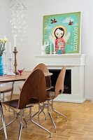 50s laminated wooden chair, round dining table and modern picture of angel on mantelpiece in background
