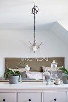 Pendant lamp with wire frame lampshade above orchids and glass ornaments on sideboard; double bed in background