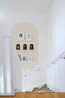 View down staircase with small gallery of framed pictures on beige panel in classic ogee shape