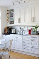 White fitted kitchen with panel doors and strip handles; dining area with vintage chairs