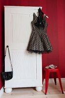 Short cocktail dress and handbag hanging from white wardrobe next to plastic stool against red striped wallpaper