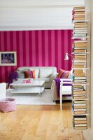 Books stacked on wall-mounted shelves; red and pink striped wallpaper in living room in background