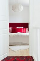 View through open door of double bed with headboard and scatter cushions in shades of red