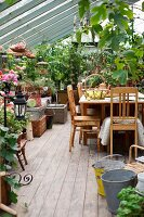 Wooden table and kitchen chairs in conservatory with planters on floor