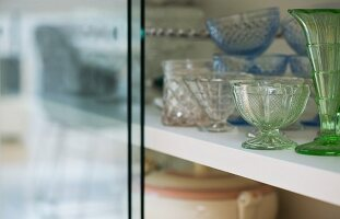 Various vintage glass vessels in glass-fronted cabinet