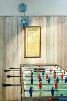 Illuminated games area with football table and simple wood-panelled wall