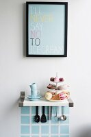 Pastries on cake stand and espresso cups on bracket shelf with kitchen utensils hung below under framed poster with motto