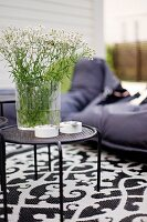 Glass vase of garden flowers on black metal side table and black and white patterned rug