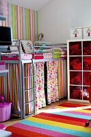 Metal loft bed with colourful curtains in corner of child's bedroom with striped rug