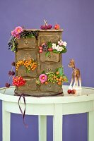Small chest of drawers decorated with autumnal berries & flowers