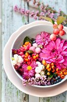 Autumnal arrangement of flowers & berries in bowl