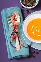Sprig of sea buckthorn decorating place setting with bowl of pumpkin and sea buckthorn soup