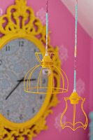Pendant lamps with yellow-painted wire lampshades in front of vintage wall clock with ornate, yellow frame