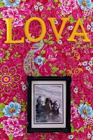 Framed family photo below yellow letters on pink, floral wallpaper