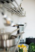 Metal racks of crockery on wall above bowl of lemons
