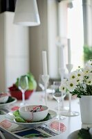 Place setting with white bowl on table mat and vase of flowers to one side