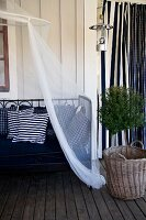Metal day bed with white and blue cushions below canopy next to small potted tree on wooden veranda floor