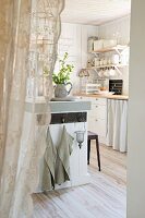 View through open doorway with white lace curtain into white country-house kitchen