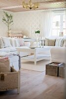 Sofa set and rustic, white-painted wooden coffee table in corner of country-style living room