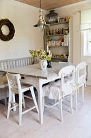 Dining table, white kitchen chairs, bench and storage containers on shelf unit in background