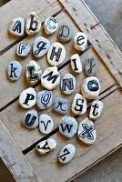 Collection of pebbles labelled with alphabet on wooden crate