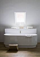 Bathtub by Philippe Starck with antique bronze tap in minimalist bathroom under skylight