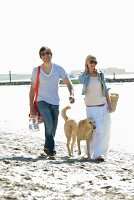 Couple and dog on their way to beach picnic
