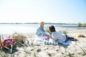 Couple and dog enjoying beach picnic