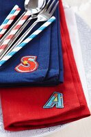 Colourful linen napkins with iron-on initials, cutlery and drinking straws