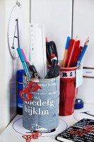 Pen holders with decoupage alphabet design on desk