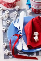 Blue plate, cutlery, napkin and alphabet decorations on place mat
