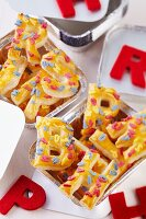 Puff pastry letters with decorations in aluminium trays