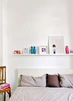 Row of pillows and cushions on bed below pictures and figurines on white floating shelf in bedroom