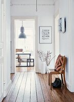 Flea-market vases and chair in bright corridor of period apartment; view of industrial lamp above DIY dining set through door at far end