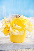 Yellow tulips and feathers in flower pot