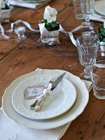 White place setting with glasses and violas on rustic wooden table