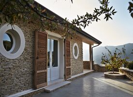 Mediterranean house with porthole windows and terrace doors with slatted wooden shutters