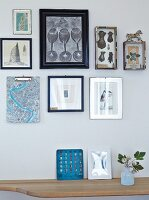 Frames pictures on wall above wooden shelf