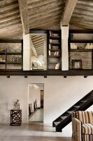 Double-height, loft-style interior in rustic, renovated country house with wood-beamed ceiling, partially visible staircase and mezzanine with fitted shelves