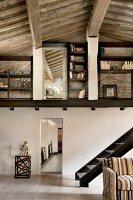 Nach oben offener Wohnraum in einem rustikalen, renoviertem Landhaus mit Holzbalkendecke, teilweise sichtbare Treppe, unter Galerie mit eingebauten Regalen; Loftcharakter