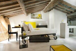Multifunktionales, mobiles Bett, an Kopfende montierte Schreibtischplatte, davor Stuhl in renoviertem Dachgeschoss mit rustikaler Holzbalkendecke