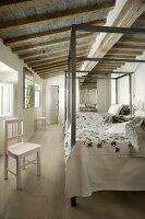 Zwei Betten mit Metall-Himmelgestell in langgestrecktem, rustikalem Schlafzimmer mit Holzbalkendecke