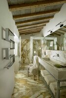Luxurious bathroom with marble floor, rustic wood-beamed ceiling and trough-style sink on metal frame with towel shelf