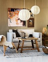 Simple paper lampshades above rustic table, wicker chair and sofa below painting by Gustav Klimt on wall