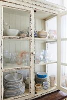 Crockery in glass-fronted cabinet with peeling white paint