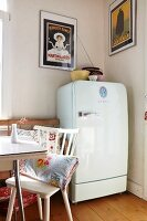 White fifties fridge in dining room with vintage advertising posters in clip-on picture frames on walls